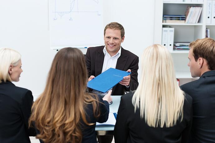 Businessman in a corporate interview handing over his curriculum vitae to one of the human resources team conducting the interview.jpeg